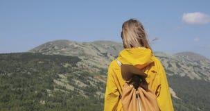 La mujer joven que camina en impermeable amarillo se coloca en las montañas almacen de metraje de vídeo