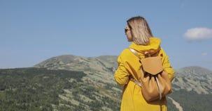 La mujer joven que camina en impermeable amarillo se coloca en las montañas metrajes