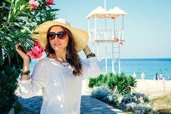 La mujer joven que camina en la playa por el rododendro florece Imagen de archivo libre de regalías