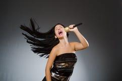 La mujer joven que canta en club del Karaoke fotografía de archivo
