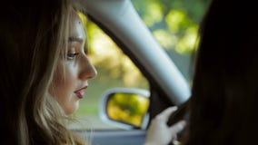 La mujer joven que conduce el coche Visión desde los asientos traseros del coche almacen de video
