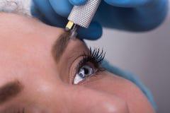 La mujer joven que consigue una ceja permanente compone el tratamiento Fotos de archivo
