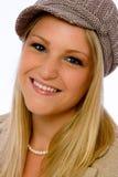 La mujer joven que desgasta el casquillo de la Mod sonríe en la cámara Fotografía de archivo libre de regalías