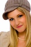 La mujer joven que desgasta el casquillo de la Mod sonríe en la cámara Foto de archivo