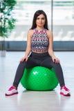 La mujer joven que ejercita con la bola suiza en concepto de la salud Foto de archivo