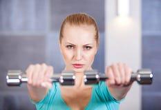 La mujer joven que ejercita con pesas de gimnasia en el entrenamiento del gimnasio lleva a hombros Imagen de archivo libre de regalías