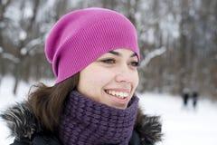 La mujer joven que el brunette en un casquillo violeta mira imagen de archivo