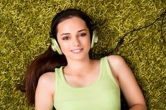 La mujer joven que escucha la música en casa Imagen de archivo libre de regalías