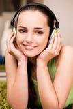 La mujer joven que escucha la música en casa Imagenes de archivo
