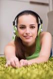 La mujer joven que escucha la música en casa Imagen de archivo