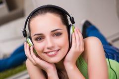 La mujer joven que escucha la música en casa Fotografía de archivo