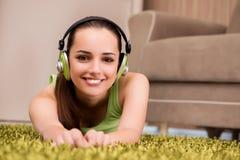 La mujer joven que escucha la música en casa Fotos de archivo