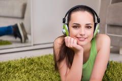 La mujer joven que escucha la música en casa Fotografía de archivo libre de regalías