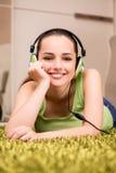 La mujer joven que escucha la música en casa Foto de archivo libre de regalías