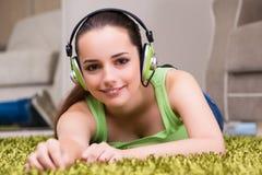 La mujer joven que escucha la música en casa Fotos de archivo libres de regalías