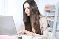 La mujer joven que estudia en el ordenador y toma notas Fotografía de archivo