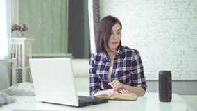 La mujer joven que estudia, usando un ayudante de la voz, tiene una pregunta
