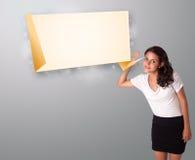 La mujer joven que gesticula con papiroflexia moderna copia el espacio Fotos de archivo