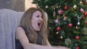 La mujer joven que grita en terror con las manos en su cabeza, articula mirar abierto de par en par en pánico la cámara almacen de video