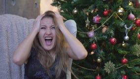La mujer joven que grita en terror con las manos en su cabeza, articula mirar abierto de par en par en pánico la cámara metrajes
