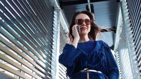 La mujer joven que habla en el teléfono móvil en la ciudad, pelo se convierte del viento almacen de metraje de vídeo