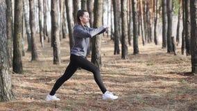 La mujer joven que hace aptitud ejercita al aire libre Muchacha apta que hace estocadas en parque metrajes