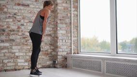 La mujer joven que hace estirar de la pierna muscles inclinarse en travesaño de la ventana almacen de metraje de vídeo