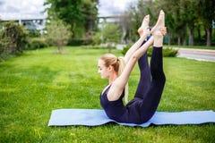 La mujer joven que hace estirar ejercita en la hierba en el parque Imagen de archivo libre de regalías