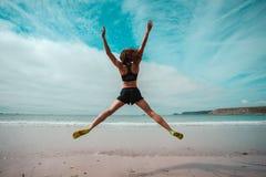 La mujer joven que hace la estrella salta en la playa imágenes de archivo libres de regalías