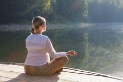 La mujer joven que hace yoga ejercita en el lago Imágenes de archivo libres de regalías
