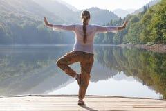 La mujer joven que hace yoga ejercita en el lago Fotos de archivo libres de regalías