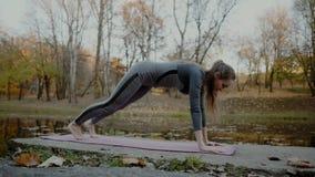 La mujer joven que hace yoga ejercita en el parque de la ciudad del otoño Concepto de la forma de vida de la salud metrajes