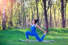 La mujer joven que hace yoga ejercita en el parque de la ciudad del verano Concepto de la forma de vida de la salud fotos de archivo libres de regalías