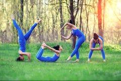 La mujer joven que hace yoga ejercita en el parque de la ciudad del verano YOGA de la palabra Concepto de la forma de vida de la  Foto de archivo