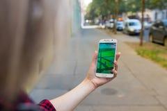 La mujer joven que juega Pokemon va al aire libre Imagenes de archivo
