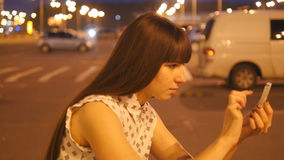 La mujer joven que juega Pokemon VA al aire libre en el estacionamiento del centro comercial, usando el teléfono elegante Muchach almacen de video
