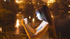 La mujer joven que juega Pokemon VA al aire libre en la noche, usando el teléfono elegante Juego de la muchacha el juego popular  metrajes