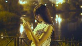 La mujer joven que juega Pokemon VA al aire libre en la noche, usando el teléfono elegante Juego de la muchacha el juego popular  almacen de video