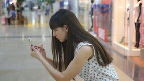 La mujer joven que juega Pokemon VA interior en el centro comercial, usando el teléfono elegante Juego de la muchacha el juego po almacen de metraje de vídeo