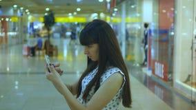 La mujer joven que juega Pokemon VA interior en el centro comercial, usando el teléfono elegante Juego de la muchacha el juego po almacen de video
