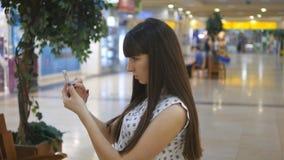 La mujer joven que juega Pokemon VA interior en el centro comercial, usando el teléfono elegante Juego de la muchacha el juego po metrajes