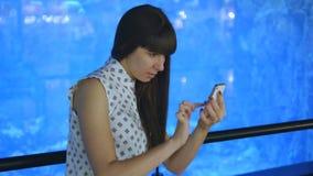 La mujer joven que juega Pokemon VA interior en el oceanarium, usando el teléfono elegante Juego de la muchacha el juego popular  almacen de metraje de vídeo