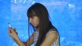 La mujer joven que juega Pokemon VA interior en el oceanarium, usando el teléfono elegante Juego de la muchacha el juego popular  metrajes