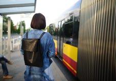La mujer joven que la morenita se coloca en la parada de autobús Foto de archivo libre de regalías