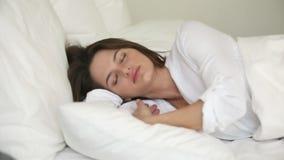 La mujer joven que lanza y que da vuelta en cama sufre de insomnio almacen de video