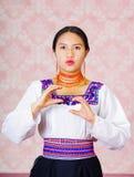 La mujer joven que lleva el vestido andino tradicional, haciendo frente a la cámara que hace la palabra del lenguaje de signos pa Fotos de archivo