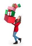 La mujer joven que lleva una pila de derrumbarse presenta Foto de archivo libre de regalías