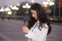 La mujer joven que mira abajo de la pantalla Imagen de archivo libre de regalías