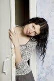 La mujer joven que mira de detrás la puerta Imágenes de archivo libres de regalías