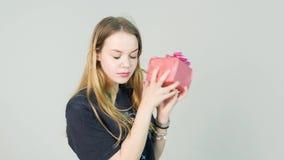 La mujer joven que mira un regalo y quiere saber qué ` s dentro en el fondo blanco almacen de video